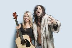 Portret gestykuluje z kobiety mienia gitarą przeciw bławemu tłu szczęśliwy młody człowiek Fotografia Royalty Free