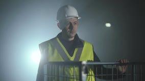 Portret glimlachende mens in de eenvormige bouwers en helm die zich voor de zwarte achtergrond met schijnwerper bevinden stock videobeelden