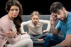 Portret gniewna córka i spęczenie wychowywa na czerni Fotografia Stock
