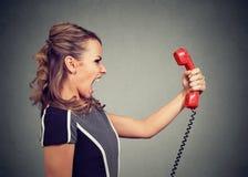 Portret gniewna kobieta wrzeszczy przy telefonem Fotografia Royalty Free
