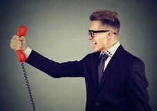 Portret gniewny biznesowy mężczyzna wrzeszczy przy telefonem obraz stock