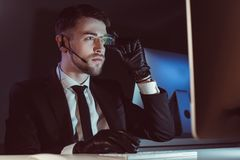 portret hacker patrzeje ekran komputerowego przy stołem z słuchawki zdjęcie stock