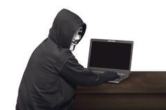 Portret hackera mężczyzna z maskowy przyglądającym z powrotem podczas gdy pisać na maszynie lapto Fotografia Royalty Free