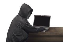 Portret hackera mężczyzna z maskowy przyglądającym z powrotem podczas gdy pisać na maszynie lapto Zdjęcie Royalty Free