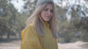 Portret het aanbiddelijke mooie jonge mooie blonde vrouw stellen dichtbij meer of rivier stock video