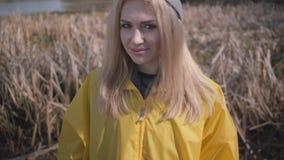 Portret het aanbiddelijke vrij jonge mooie blonde vrouw stellen dichtbij meer of rivier stock footage