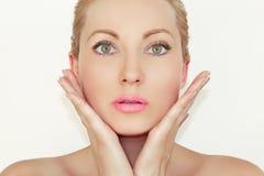 Portret Het close-up van een mooie jonge vrouwenholding overhandigt dichtbij het gezicht Het concept gezonde en bevochtigde huid stock foto