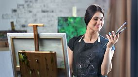 Portret het gelukkige kunstenaar vrouwelijke stellen dichtbij schildersezel met canvas tijdens werken die camera bekijken stock footage
