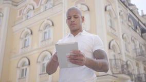 Portret het knappe kale zakenman typen van het Middenoosten op de tablet die op de stadsstraat tanding Freelance concept stock footage