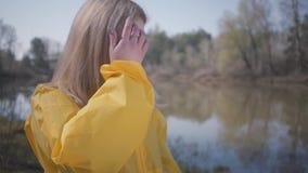 Portret het leuke jonge mooie blonde vrouw stellen dichtbij meer of rivier stock videobeelden