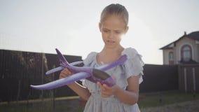 Portret het leuke meisje spelen met het kleine stuk speelgoed vliegtuigclose-up De kind het besteden tijd in openlucht in de binn stock footage
