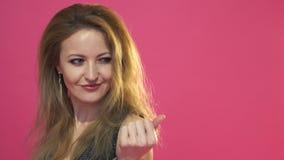 Portret het mooie vrouw uitnodigen voor iemand of iets Studio op roze achtergrond wordt geschoten die stock footage