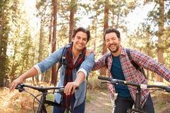 Portret Homoseksualny Męski pary kolarstwo Przez spadku lasu Obrazy Stock