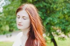 Portret imbirowa dziewczyna w zieleni z oczami zamykającymi Fotografia Stock
