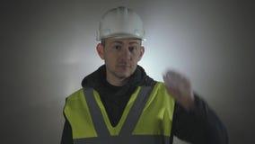 Portret industriële ingenieurs in bouwvakker op een zwarte achtergrond in de schijnwerper stock footage