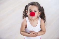 Portret jest ubranym błazenu śliczna mała dziewczynka ostrożnie wprowadzać w domu Zdjęcia Royalty Free