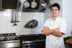 Portret Jest ubranym biel Stoi kuchenką W kuchni szef kuchni Zdjęcia Stock