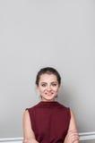 Portret jest ubranym biznesów ubrania patrzeje kamerę z uśmiechem ładna młoda kobieta, stoi przeciw popielatej ścianie Obrazy Royalty Free