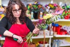 Portret jest ubranym fartuch pozycję przy odpierającym robi bukietem dla klienta przy kwiatu sklepem kobiety kwiaciarnia zdjęcie royalty free
