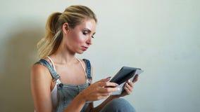 Portret jest ubranym jednolitego działanie na budowie młoda kobieta, patrzeje cyfrową pastylkę zbiory wideo