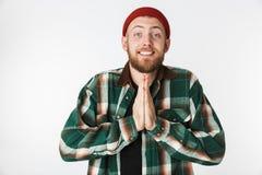 Portret jest ubranym kapeluszu i szkockiej kraty koszula utrzymuje palmy togerther dla emocjonalny mężczyzna ono modli się, podcz fotografia royalty free