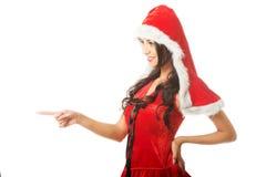 Portret jest ubranym Santa ubrania i wskazuje lewica piękna kobieta zdjęcia stock