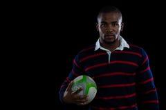 Portret jest ubranym sporty rugby gracz munduruje mienie piłkę zdjęcie stock