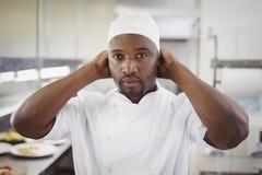 Portret jest ubranym szefów kuchni kapeluszowych w handlowej kuchni uśmiechnięty szef kuchni Zdjęcie Royalty Free
