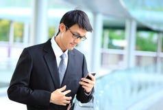 Portret jest ubranym szkła i używa smartpho młody biznesmen Zdjęcia Stock