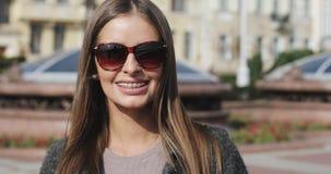 Portret jong meisje die met steunen op tanden camera en het glimlachen bekijken stock video