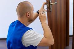 Portret Jonge Mannelijke Timmerman Repairing Door Lock stock afbeeldingen