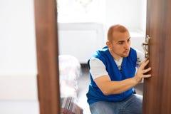 Portret Jonge Mannelijke Timmerman Repairing Door Lock stock fotografie