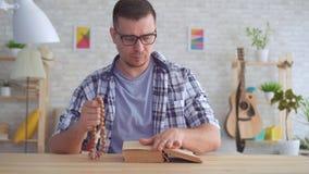Portret jonge mens met glazen met een rozentuin in zijn handen en lezing de Bijbel stock footage