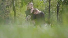 Portret jonge moeder en haar tienerzoon die in het park samen rusten Gelukkige vriendschappelijke familie De aanbiddelijke jongen stock videobeelden