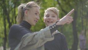 Portret jonge moeder en haar tienerzoon die in het park samen rusten Gelukkige vriendschappelijke familie Vrije tijd in openlucht stock video