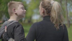 Portret jonge moeder en haar tienerzoon die in het park samen rusten Gelukkige vriendschappelijke familie Vrije tijd in openlucht stock footage