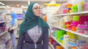 Portret jonge moslimvrouw in hijab in de supermarkt in het Ministerie van huishoudengoederen stock videobeelden