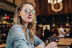 Portret jonge onderneemster in modieuze glazen die, die in koffie voor computer zitten en nota's in notitieboekje nemen royalty-vrije stock foto
