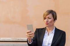 Portret jonge onderneemsters in zwart kostuum die smartphone gebruiken Stock Afbeelding