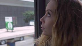 Portret jonge vrouw die aan de bus kijken van de vensterpassagier terwijl het berijden op moderne stadsstraat Mooie vrouwenzittin stock videobeelden