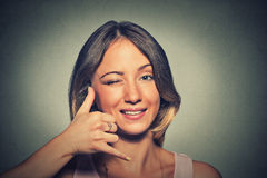 Portret jonge vrouw die tot wijzerplaat maken mijn aantalteken met hand zoals telefoon Royalty-vrije Stock Foto's