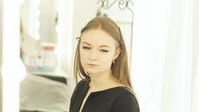 Portret jonge vrouw met klem op haar tijdens make-up in kleedkamer De model voorspiegel van de gezichtsmake-up terwijl binnen opl stock videobeelden