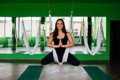 Portret jonge vrouwen die antigravity yogaoefeningen maken De luchttraining van de de geschiktheidstrainer van de aerovlieg witte stock foto's