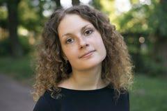 Portret kędzierzawa dziewczyna w czarnej sukni outdoors obraz royalty free