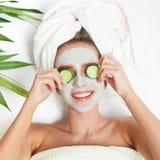 Portret kłaść z ręcznikiem na głowie piękno kobieta, ogórek na ona oczy, twarzowa maska kwiat na tło miski czworonożne płatkiem t fotografia royalty free