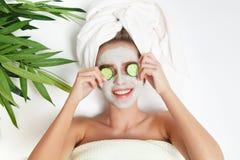 Portret kłaść z ręcznikiem na głowie piękno kobieta, ogórek na ona oczy, twarzowa maska kwiat na tło miski czworonożne płatkiem t Obrazy Royalty Free