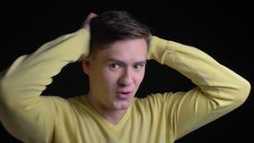 Portret Kaukasische mens op middelbare leeftijd in gele sweater die extreem geluk tonen in camera op zwarte achtergrond stock footage