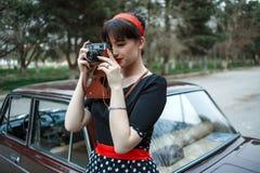 Portret Kaukaska piękna młoda dziewczyna w czarnego rocznika smokingowy pozować z rocznik kamerą w rękach zdjęcia royalty free