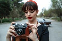 Portret Kaukaska piękna młoda dziewczyna w czarnego rocznika smokingowy pozować z rocznik kamerą w rękach obraz royalty free