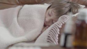Portret kleine jongen die die op de bank liggen met een deken thuis wordt behandeld Het leuke kind rust De jongen is ziek, voelt  stock video